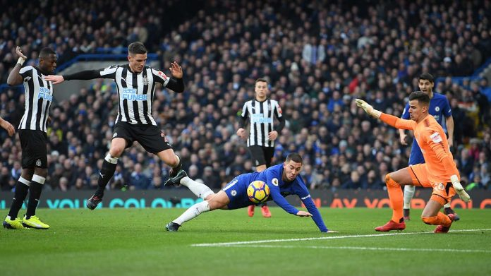 Eden Hazard goes down under the challenge of Ciaran Clark of Newcastle United during the Premier League match between Chelsea and Newcastle United at Stamford Bridge on December 2, 2017 in London.