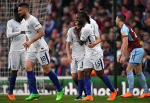 Chelsea players celebrate their first goal, an own goal scored by Kevin Long of Burnley (not pictured) during the Premier League match between Burnley and Chelsea at Turf Moor on April 19, 2018 in Burnley, England.