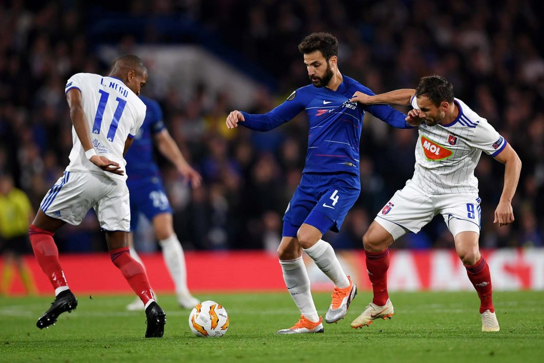 Cesc Fabregas battles for possession with Loic Nego and Szabolcs Huszti of MOL Vidi FC during the UEFA Europa League Group L match between Chelsea and Vidi FC at Stamford Bridge on October 4, 2018 in London.