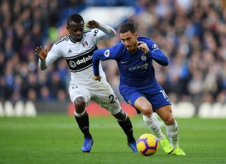 Eden Hazard runs with the ball under pressure from Jean Michael Seri of Fulham during the Premier League match between Chelsea FC and Fulham FC at Stamford Bridge on December 1, 2018 in London.