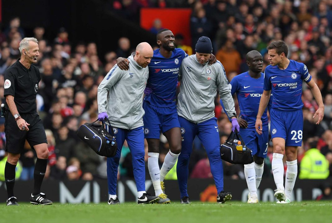 An injured Antonio Rudiger is given assistance during the Premier League match between Manchester United and Chelsea FC at Old Trafford on April 28, 2019 in Manchester.