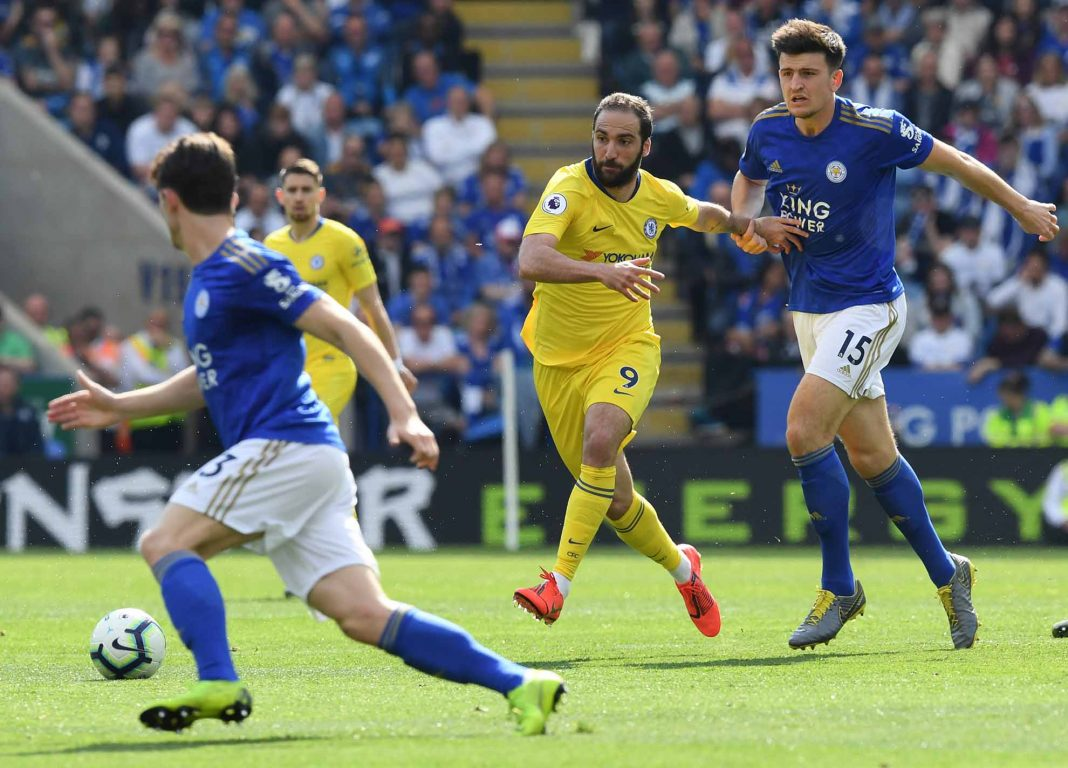 Gonzalo Higuain is challenged by Harry Maguire of Leicester City during the Premier League match between Leicester City and Chelsea FC at The King Power Stadium on May 12, 2019 in Leicester.