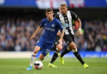 Christian Pulisic of Chelsea runs with the ball under pressure from Joelinton of Newcastle United during the Premier League match between Chelsea FC and Newcastle United at Stamford Bridge on October 19, 2019 in London.